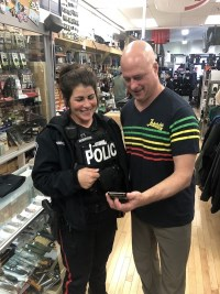 officer and person looking at mobile device in store